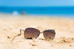 Gafas de sol en la arena de la playa y el fondo del mar Fotografía de archivo libre de regalías