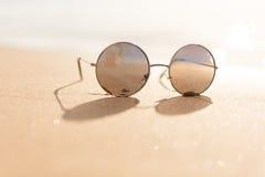 Gafas de sol en la arena de la playa y el fondo del mar Imágenes de archivo libres de regalías
