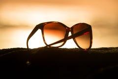 Gafas de sol en la puesta del sol Imágenes de archivo libres de regalías