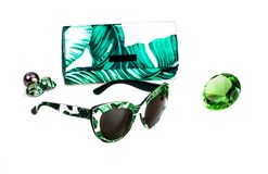 Gafas de sol en marco blanco-verde plástico conjuntamente con una cubierta en un fondo blanco imagenes de archivo