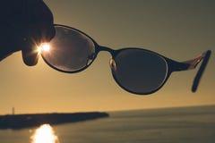 Gafas de sol en un fondo de la puesta del sol del mar Imagenes de archivo