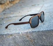 Gafas de sol en un marco de madera en pasos de piedra grises Fotografía de archivo