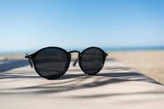 Gafas de sol en un ocioso del sol con el mar en frente Imagenes de archivo