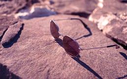 Gafas de sol en una roca foto de archivo libre de regalías