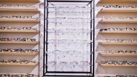 Gafas de sol en una tienda Una colección de bastidores en el estante de una tienda metrajes