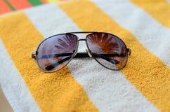 Gafas de sol en una toalla agudeza Imagen de archivo