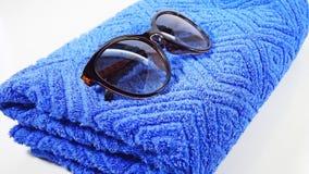 Gafas de sol en una toalla azul Foto de archivo libre de regalías