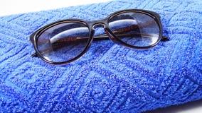 Gafas de sol en una toalla azul Fotos de archivo
