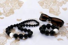 Gafas de sol, granos y pulsera en la bufanda Imagen de archivo libre de regalías