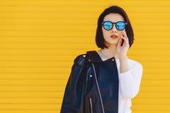 Gafas de sol hermosas de la muchacha en fondo amarillo brillante Fotos de archivo libres de regalías