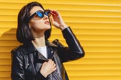 Gafas de sol hermosas de la muchacha en fondo amarillo brillante Fotografía de archivo