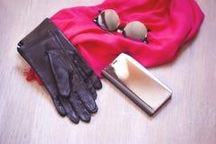 Gafas de sol de la caja y del espejo del tel?fono del espejo y bufanda rosada en la tabla de madera fotos de archivo libres de regalías