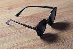 Gafas de sol de la moda en la tabla de madera Imagen de archivo