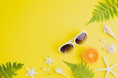 Gafas de sol de los accesorios de la playa, estrellas de mar, naranja, hojas del helecho y c?scara del mar en el fondo amarillo p foto de archivo