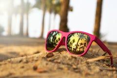 Gafas de sol modernas rosadas en la arena de la playa con las palmeras y puesta del sol foto de archivo