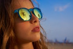 Gafas de sol morenas de la muchacha con la palmera Foto de archivo libre de regalías