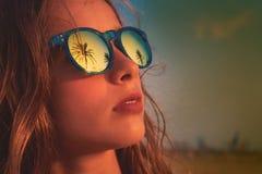 Gafas de sol morenas de la muchacha con la palmera Imagen de archivo libre de regalías