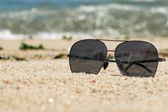 Gafas de sol oscuras en la playa arenosa en verano con las olas oceánicas en fondo fotos de archivo
