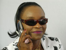 Gafas de sol que desgastan de la mujer negra que dan una llamada Imágenes de archivo libres de regalías