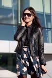 Gafas de sol que desgastan de la mujer que hablan por el teléfono Imagenes de archivo