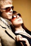 Gafas de sol que desgastan de los pares jovenes de moda Fotos de archivo