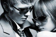Gafas de sol que desgastan de los pares jovenes de moda Fotografía de archivo libre de regalías
