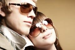 Gafas de sol que desgastan de los pares jovenes de moda Imagen de archivo