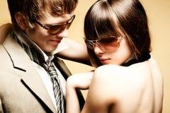 Gafas de sol que desgastan de los pares jovenes de moda Fotografía de archivo