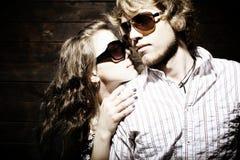 Gafas de sol que desgastan de los pares jovenes de moda Imagen de archivo libre de regalías