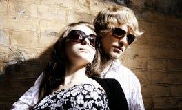 Gafas de sol que desgastan de los pares jovenes de moda Foto de archivo libre de regalías