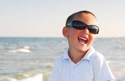 Gafas de sol que desgastan del muchacho por el mar Foto de archivo