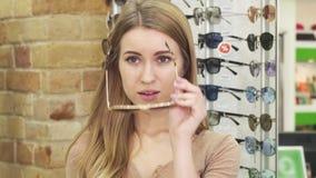 Gafas de sol que intentan sonrientes imponentes de la mujer joven en la tienda de las gafas almacen de metraje de vídeo