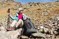 Gafas de sol que llevan abajo chaqueta y sombrero de una muchacha turística con un equipo de la mochila y de la montaña con las m Imágenes de archivo libres de regalías