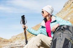 Gafas de sol que llevan abajo chaqueta y sombrero de una muchacha turística con un equipo de la mochila y de la montaña con las m Fotografía de archivo