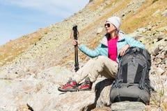 Gafas de sol que llevan abajo chaqueta y sombrero de una muchacha turística con un equipo de la mochila y de la montaña con las m Imagen de archivo