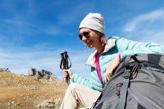 Gafas de sol que llevan abajo chaqueta y sombrero de una muchacha turística con un equipo de la mochila y de la montaña con las m Fotografía de archivo libre de regalías