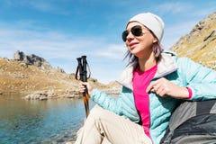 Gafas de sol que llevan abajo chaqueta y sombrero de una muchacha turística con un equipo de la mochila y de la montaña con las m Foto de archivo libre de regalías