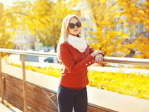 Gafas de sol que llevan de la mujer bastante rubia y chaqueta roja con la bufanda en otoño soleado Imagen de archivo libre de regalías