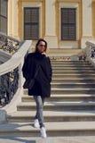 Gafas de sol que llevan de la mujer de moda que caminan abajo de un vuelo exterior de las escaleras de piedra Fotografía de archivo
