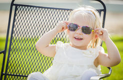 Gafas de sol que llevan del bebé juguetón lindo afuera en el parque fotografía de archivo libre de regalías
