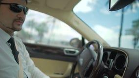 Gafas de sol que llevan del hombre de negocios que conducen el automóvil costoso, transporte almacen de metraje de vídeo