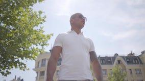Gafas de sol que llevan del hombre de Oriente Medio calvo acertado confiado y camiseta blanca El individuo hermoso del negocio mi metrajes