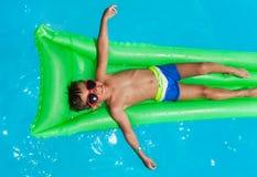 Gafas de sol que llevan del muchacho que se relajan en el colchón imagen de archivo