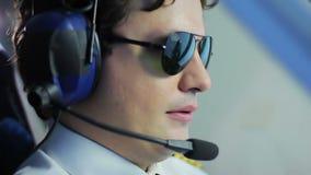 Gafas de sol que llevan experimentales jovenes y avión de pasajeros de dirección, profesión prestigiosa metrajes