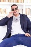 Gafas de sol que llevan felices del hombre moderno que hablan en el teléfono Fotografía de archivo