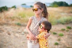 Gafas de sol que llevan hermosas de la niña y del muchacho que abrazan en campo en verano Foto de archivo libre de regalías