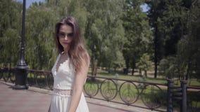 Gafas de sol que llevan de la chica joven hermosa y un vestido blanco largo de la moda del verano que camina al aire libre Ocio d metrajes