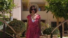 Gafas de sol que llevan de la mujer caucásica hermosa, sombrero y vestido rojo caminando hacia la cámara en el jardín con las pal almacen de metraje de vídeo