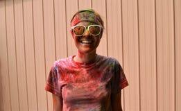 Gafas de sol que llevan sonrientes de la muchacha y cubierto en polvo coloreado Imágenes de archivo libres de regalías