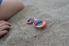 Gafas de sol rayadas en la arena fotografía de archivo libre de regalías